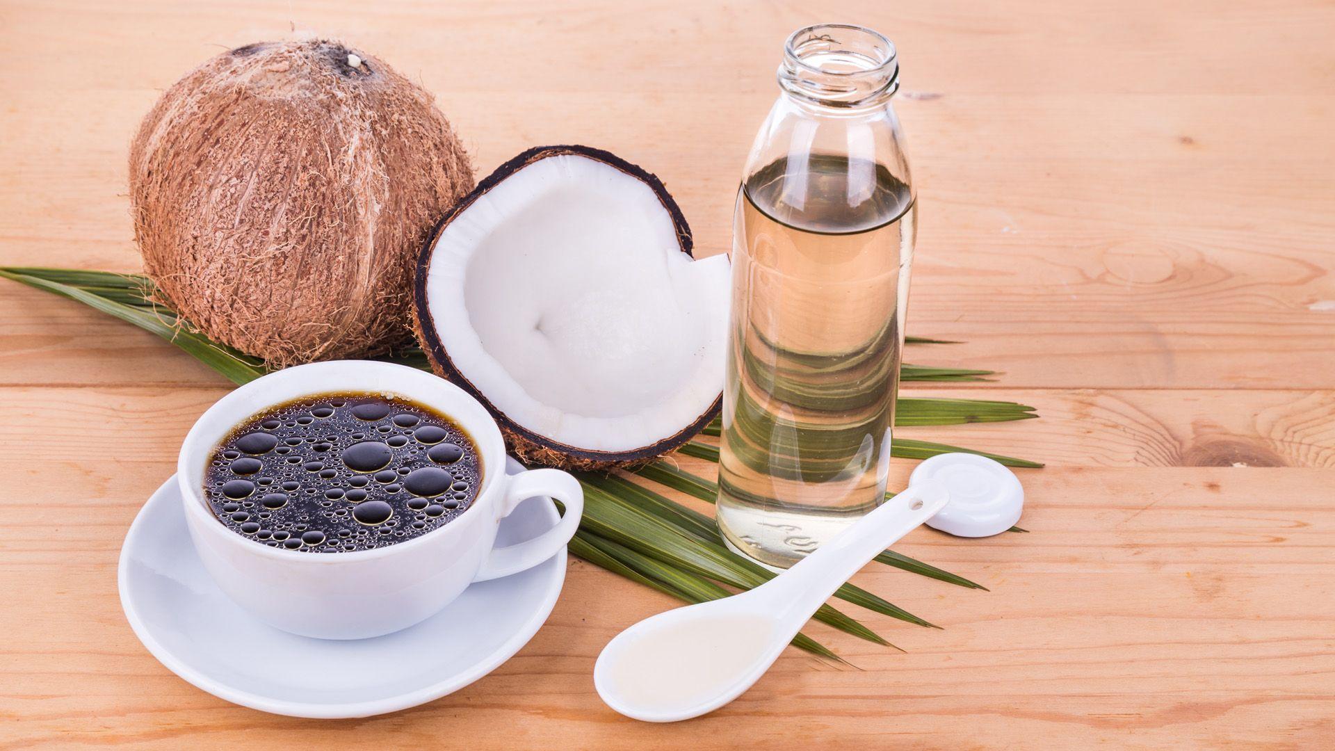 Eine Tasse Bulletproof-Coffee, eine Kokosnuss, ein Flasche und ein Löffel mit Kokosnussöl auf einem hellen Holztisch von Lidl Österreich