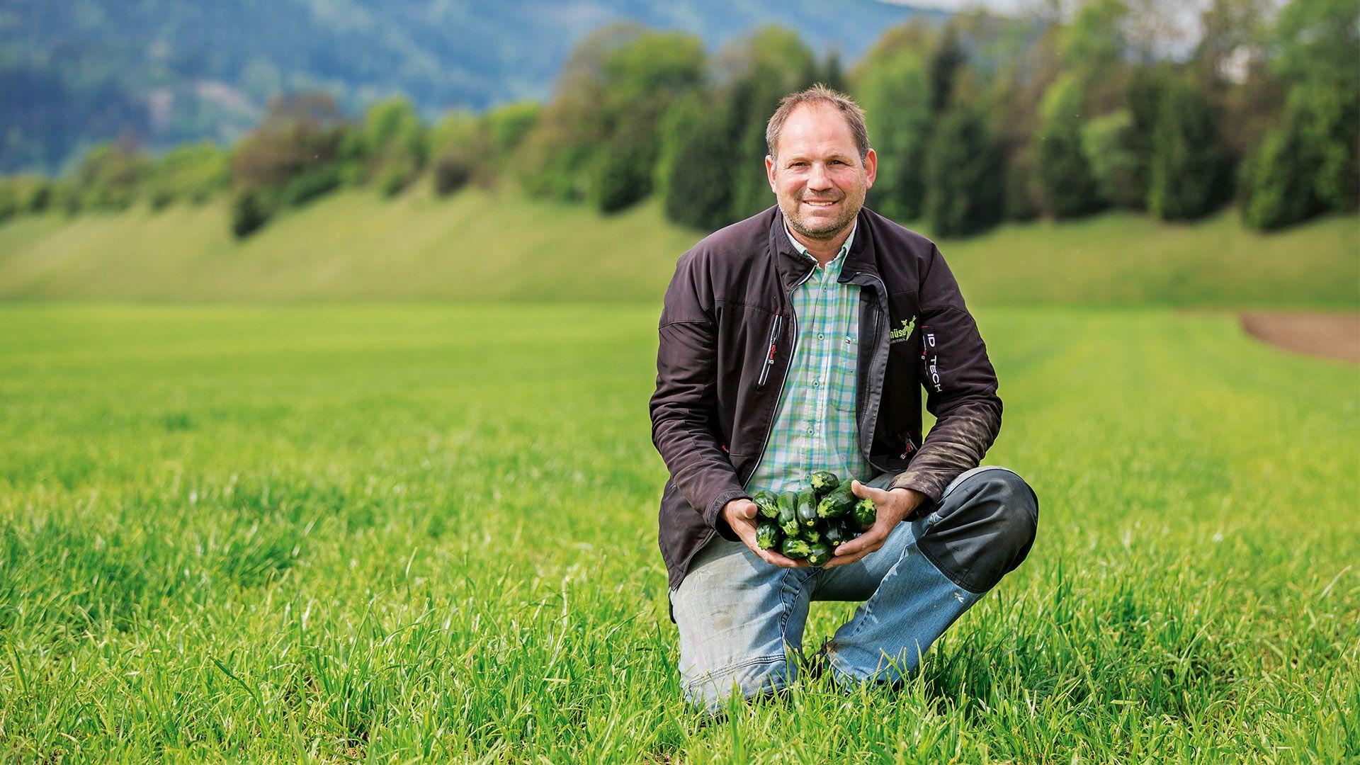 Der Zucchini-Bauer Walter Plank auf seinem Feld mit Zucchini in seinen Händen für Lidl Österreich