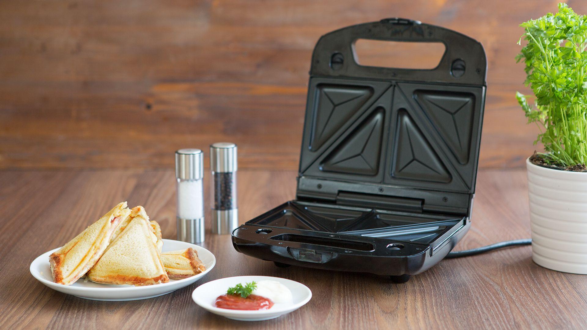 Zubereitungstipp Sandwichtoaster auf dunklem Holztisch mit einem Teller mit Toasts von Lidl Österreich